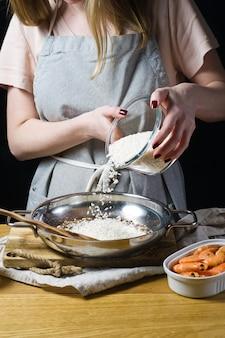 Der küchenchef gibt den reis für italienisches risotto in die pfanne.