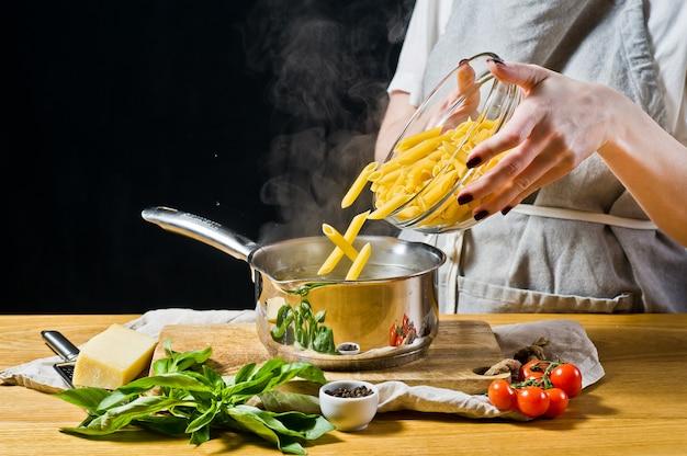 Der küchenchef gießt die pasta penne in einen topf mit kochendem wasser.