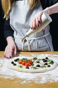 Der küchenchef gießt olivenöl auf die rohe focaccia.