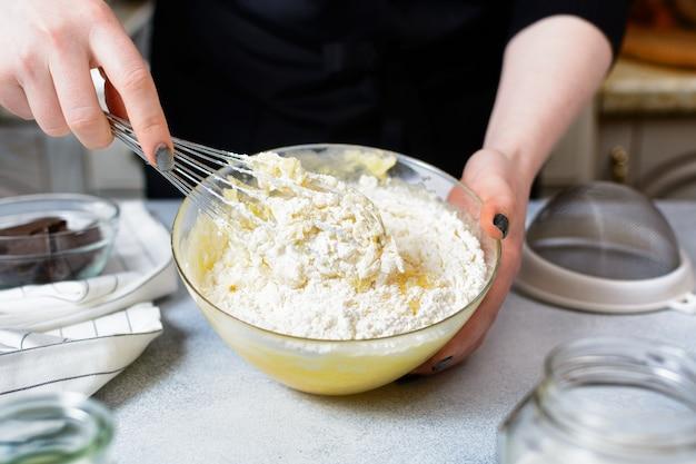 Der küchenchef hält einen metallbesen und eine glasschüssel mit mehlteig in den händen