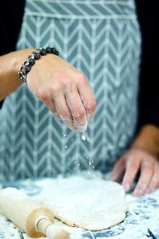 Der küchenchef kocht den teig, der mit mehl bestreut ist, das in bewegung gefriert