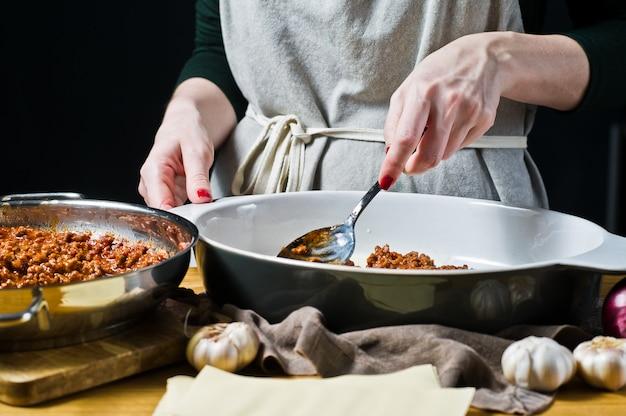 Der küchenchef kocht hausgemachte lasagne
