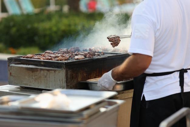 Der küchenchef nimmt gebratene heiße fleischstücke mit einer zange vom grill und legt sie auf den teller.