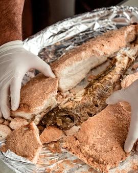 Der küchenchef öffnet salz aus fisch mit salzkruste und enthüllt zarten gekochten fisch