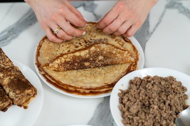 Der küchenchef rollt einen pfannkuchen mit fleischfüllung auf