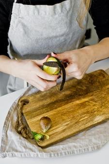 Der küchenchef schält avocado auf einem hölzernen schneidebrett.