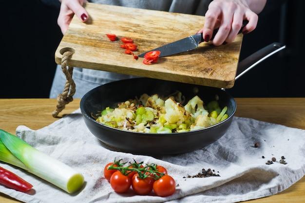 Der küchenchef schneidet chilischoten auf einem hölzernen schneidebrett.