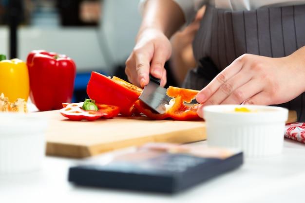 Der küchenchef schneidet die paprika auf dem hackklotz in der küche