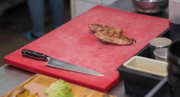 Der küchenchef schneidet frisch gekochtes, aromatisches hühnchen für gäste in einer kneipe