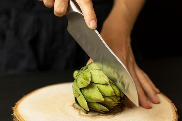 Der küchenchef schneidet frische bio-artischocken auf einem vintage-holzbrett.