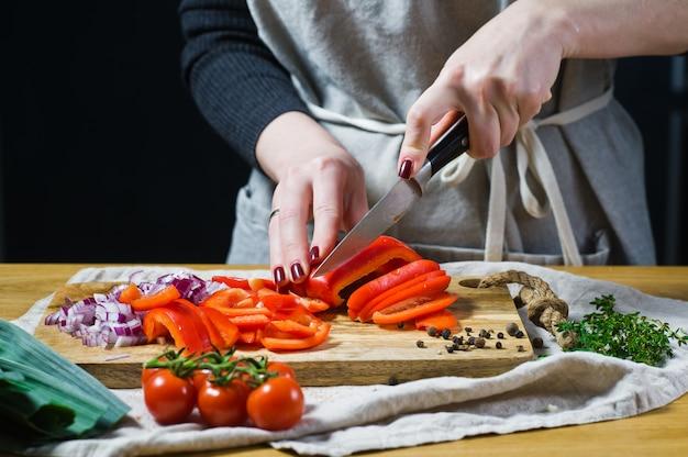 Der küchenchef schneidet rote paprikaschoten auf einem hölzernen schneidebrett.