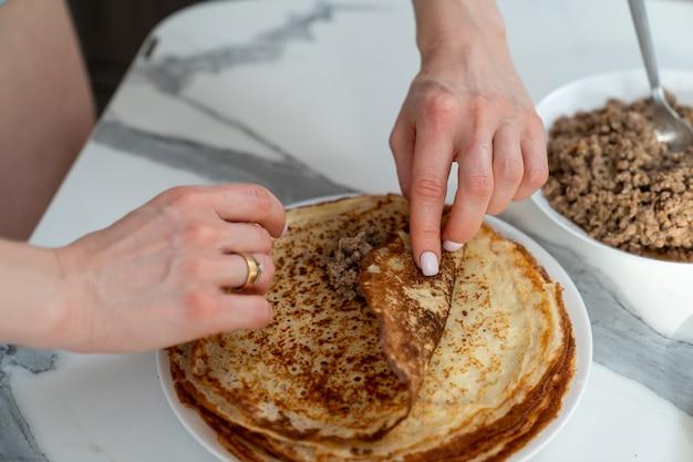 Der küchenchef wickelt die fleischfüllung in einen pfannkuchen
