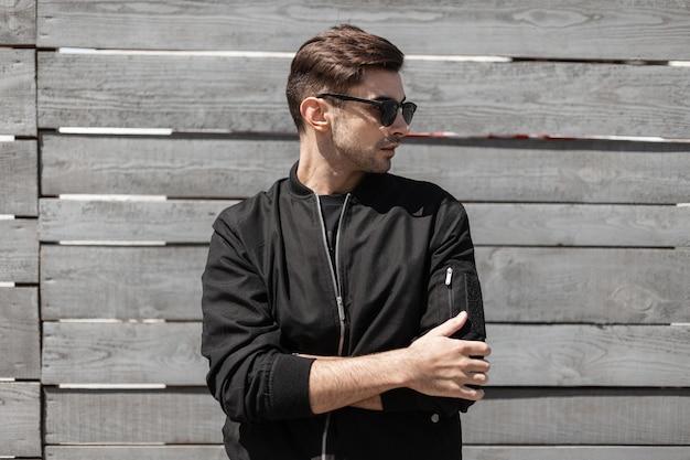 Der kühle amerikanische junge mann in der stilvollen dunklen sonnenbrille in der trendigen schwarzen jacke stellt nahe einer weinlese-holzwand auf der straße auf. attraktiver moderner typ mit einer modischen frisur. herrenbekleidung.