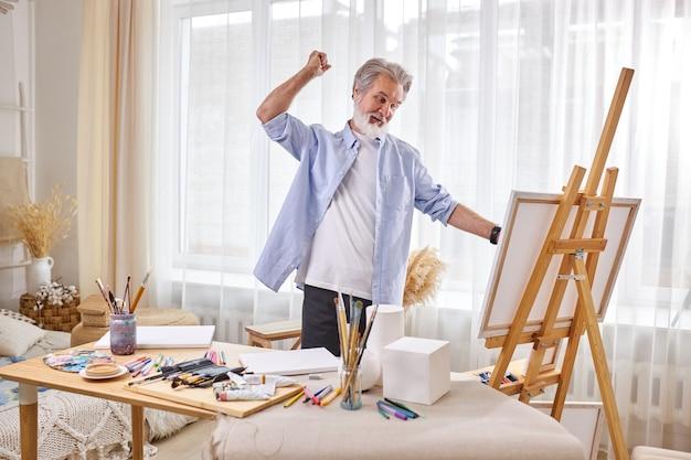 Der künstler betrachtet seine geschaffene kunst, ist zufrieden mit der arbeit, lächelt und hebt die hände, isoliert im atelierraum