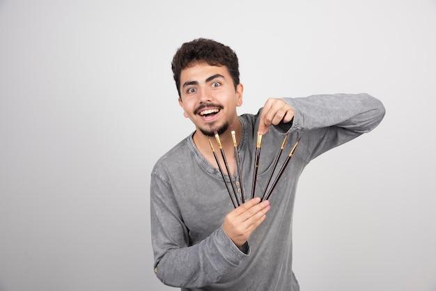 Der künstler hält seine brandneuen pinsel in der hand und fühlt sich sehr inspiriert, kunst zu schaffen.