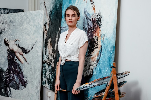 Der künstler malt abstrakte ölgemälde und arbeitet in einem gemütlichen atelier an einem gemälde