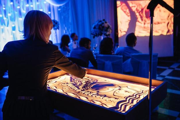 Der künstler malt plot paintings mit sand auf einem beleuchteten tisch