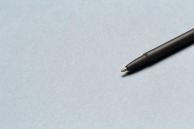 Der kugelschreiber, der kommunikation zeigt, treten mit uns in verbindung oder verschicken konzept auf grau