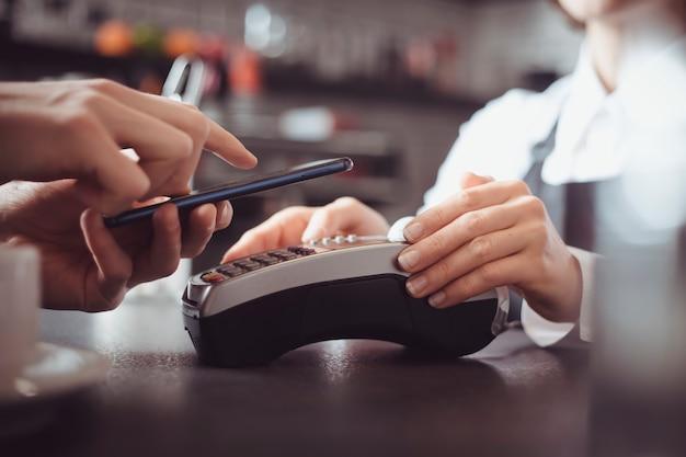Der kunde bezahlt im café mit einem mobiltelefon mit nfc-technologie