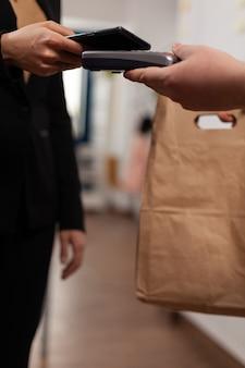 Der kunde bezahlt seine bestellung mit der smartphone-nfc-technologie