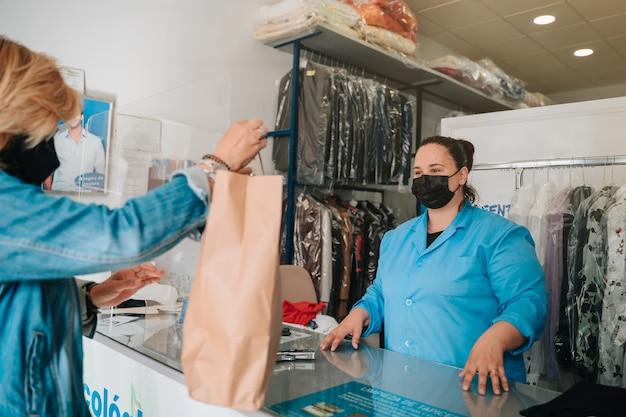 Der kunde bringt kleidung mit flecken in die chemische reinigung, damit sie von einem fachmann gereinigt werden kann