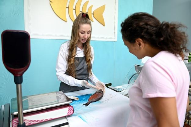 Der kunde, der einen dorado-fisch kauft, besprüht mit gewürzen von einem koch, einer fischfrau im meeresfrüchteladen. einzelhandel mit meeresfrüchten. konzept des lebensmittelkonsums