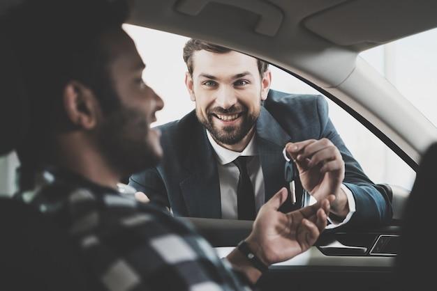 Der kunde erhält die schlüssel von manager car deal.