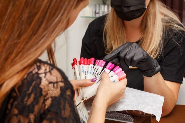 Der kunde im salon der maniküre wählt die farbe des nagellacks.