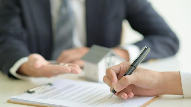 Der kunde unterzeichnet einen wohnungsbaudarlehensvertrag mit einem bankangestellten.