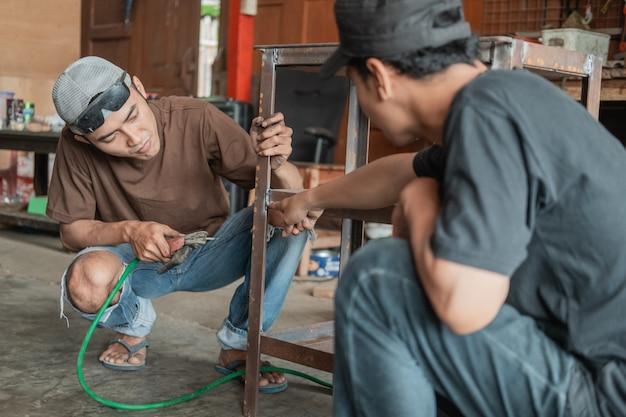 Der kunde zeigt mit dem finger auf das zu schweißende teil in der werkstatt der schweißwerkstatt