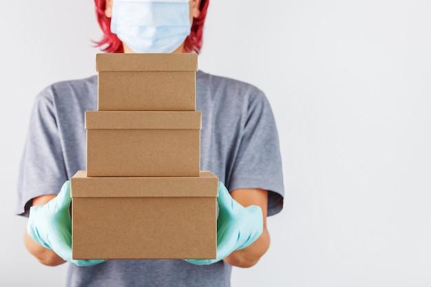 Der kurier hält ein paket pappkartons mit blauen gummihandschuhen in der hand.