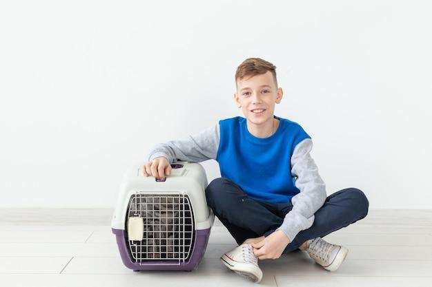 Der lachende kleine positive junge hält einen käfig mit einer schottischen katzenfalte neben sich, die auf dem boden sitzt
