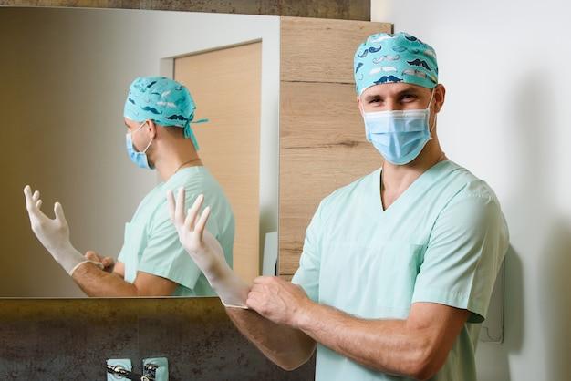 Der lächeln-chirurg zieht sterile medizinische handschuhe an und schaut nach vorne