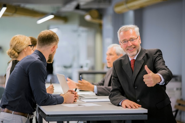 Der lächelnde ältere geschäftsmann, der daumen herauf zeichen vor den wirtschaftlern sich besprechen im büro zeigt