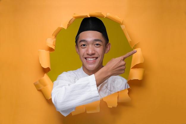 Der lächelnde asiatische muslimische teenager-mann posiert durch zerrissenes gelbes papierloch, trägt muslimisches tuch mit schädelkappe und zeigt einen kopienraum, um etwas darzustellen.