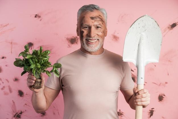 Der lächelnde, attraktive, ältere mann hält gewachsenes grün und eine schaufel in den händen