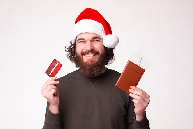 Der lächelnde bärtige mann ist glücklich, seine tickets mit bargeld von seiner karte zurückzuzahlen.
