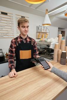 Der lächelnde barista akzeptiert die zahlung vom mobiltelefon über den pos-automaten im café. der kunde, der ein telefon in der nähe des nfc-terminals hält, macht kontaktloses mobiles bezahlen.