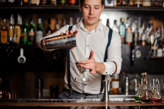 Der lächelnde barkeeper schüttelt einen schicken cocktail