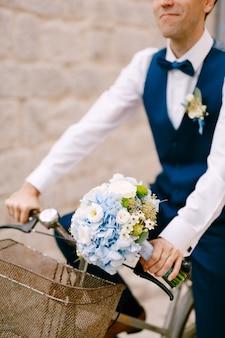 Der lächelnde bräutigam mit einem blumenstrauß fährt fahrrad