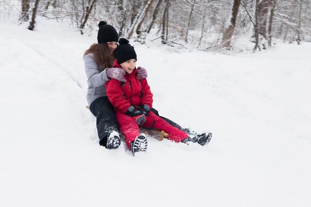Der lächelnde bruder und die schwester, die schlitten genießen, reiten zusammen in winter