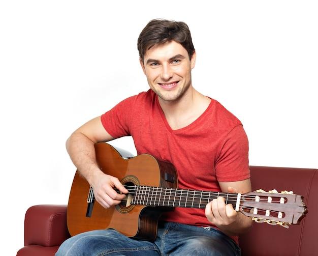 Der lächelnde gitarrist spielt auf akustischem gitarrenisolat auf weiß. hübscher junger mann sitzt mit gitarre auf diwan