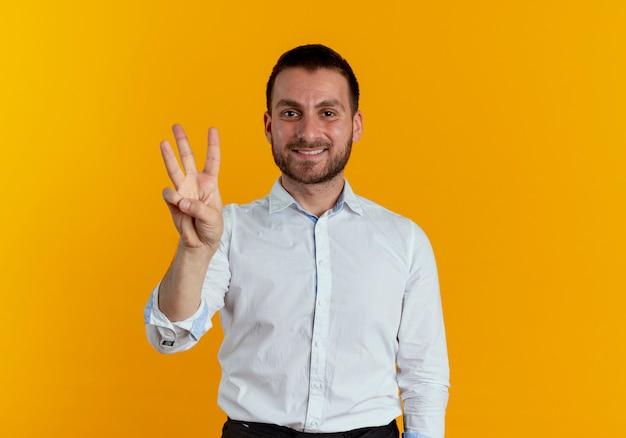 Der lächelnde gutaussehende mann gestikuliert drei mit den fingern, die auf der orangefarbenen wand isoliert sind