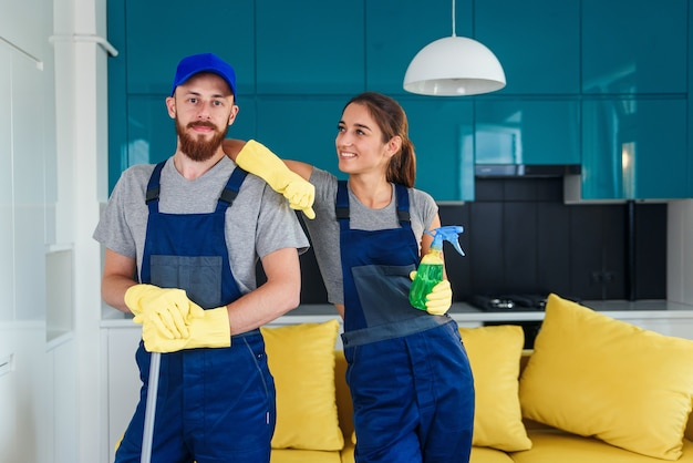 Der lächelnde, gutaussehende mann und die attraktive junge frau als professionelle reinigungskraft bleiben in der modernen küche mit reinigungsmitteln zusammen.