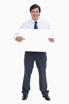 Der lächelnde händler, der auf leeres zeigt, unterzeichnen herein seine hände