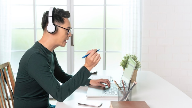 Der lächelnde hübsche asiatische geschäftsmann trägt kopfhörer, die von zu hause aus arbeiten. er ist webinar videokonferenz