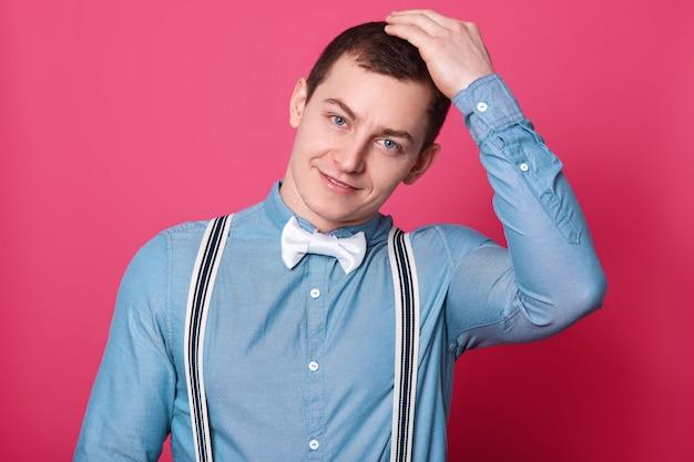 Der lächelnde hübsche junge mann legt seine hand auf den kopf, sieht fröhlich aus und posiert isoliert über der rosa wand. das schwarzhaarige sportmodell trägt ein blaues hemd, ausgezogene hosenträger und eine weiße fliege.