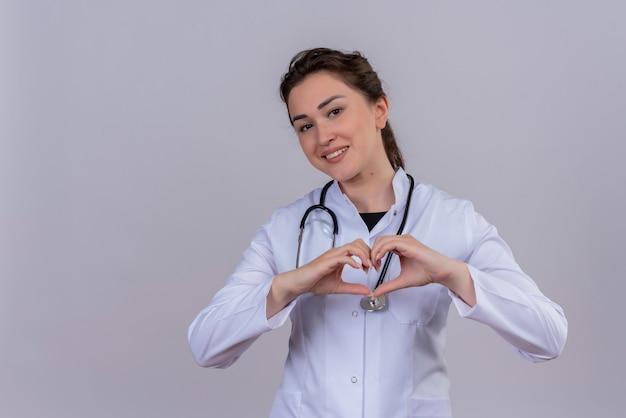 Der lächelnde junge arzt, der das medizinische kleid trägt, das stethoskop trägt, zeigt herzgeste auf weißer wand