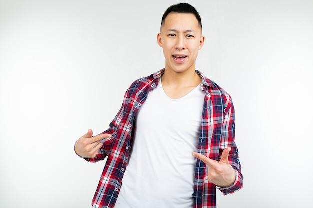 Der lächelnde junge asiatische mann in einem weit geöffneten karierten hemd zeigt leerzeichen auf seinem weißen t-shirt auf einem isolierten weißen studio