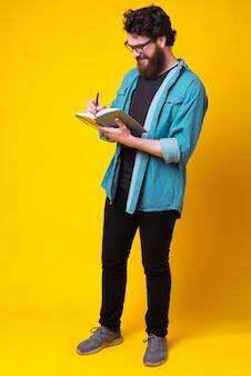 Der lächelnde junge bärtige hipster schreibt in seinem tagebuch weiter.